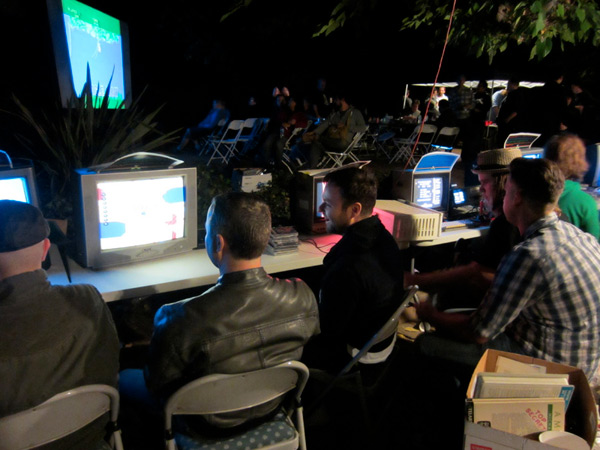 Players crowd around the consoles. Is that Jungle Hunt on the projection screen in the back?